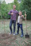 种植家谱 种植树的愉快的年轻人,当他的帮助他时的弟弟 变褐环境叶子去去的绿色拥抱本质说明说法口号文本结构树的包括的日地球 我们做着 免版税图库摄影