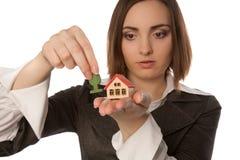 种植玩具树的女实业家在玩具房子(在h的焦点附近 免版税库存图片
