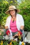种植花的资深妇女在庭院里 免版税库存图片