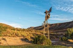 种田与一台残破的风车的场面在日落 免版税库存照片