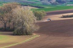 种田与犁的和喷洒的布朗春天调遣的红色耙的BlueTractor风景看法  运转在增殖比的小蓝色拖拉机 免版税库存照片