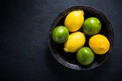种田在土气碗的新鲜的柠檬和石灰果子 免版税库存图片