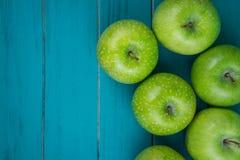 种田在木减速火箭的蓝色桌上的新鲜的有机绿色苹果与 库存图片