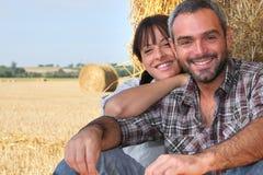 种田干草坐的夫妇 库存图片