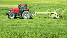 种田干草拖拉机的农夫 免版税库存图片