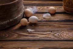 种田新鲜的有机鸡鸡蛋和羽毛在土气木背景 复活节 免版税库存图片