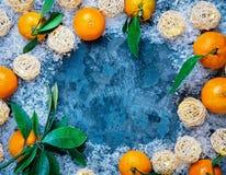 种田新鲜的橘子结果实与在土气灰色布料背景的叶子 库存照片