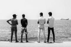 """科伦坡,斯里兰卡†""""201 2月10日, :站立在海边的四个年轻人 库存图片"""