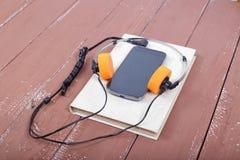 科学和教育-在木tabl的Audiobook智能手机 免版税库存图片