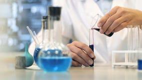 科学实验室研究员执行测试与蓝色液体 关闭 股票录像