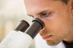年轻科学家与显微镜一起使用 库存图片