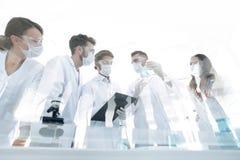 科学家与试管和显微镜一起使用在实验室里 免版税图库摄影