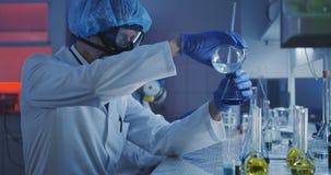 科学家倾吐的液体到圆锥形烧瓶 股票视频
