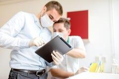 科学家做实验和学会从片剂的大学生 免版税库存照片