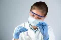 科学家和紫罗兰色管 免版税库存图片