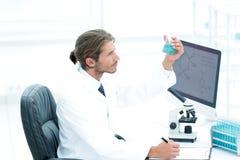 科学家在化工实验室审查有物质的一个烧瓶 免版税库存照片
