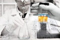 科学家在科学家手上做着实验,试剂的滴定法在烧瓶的,管 免版税库存图片