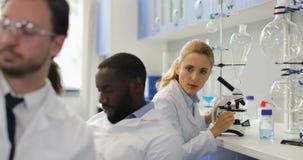 科学家妇女与显微镜一起使用,当给她的分析现代实验室的时男性同事试管 股票视频
