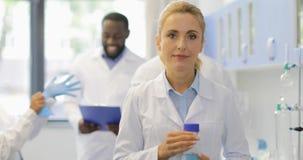 科学家妇女有化工液体愉快微笑的举行瓶在现代的谈的研究员混合种族队 影视素材