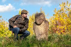 科学家审查在土墩的胡子石雕塑 免版税库存图片
