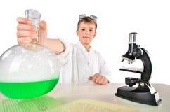 科学家男孩在他的手上拿着有绿色起泡沫的液体incide的一个大烧瓶 库存照片