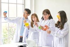 科学概念 化学家科学测试的质量 工作在实验室的队科学家 一个男性和三女性在化学 免版税库存照片