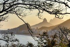 科帕卡巴纳海滩在日落期间的里约热内卢在植被之间 免版税库存图片