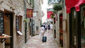 科托尔,黑山- 2017年6月27日, 运载行李的资深妇女走通过老城市狭窄的街道由石头 影视素材