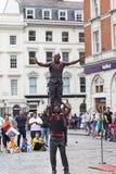 科文特花园市场、普遍的购物和旅游胜地,在街道,伦敦,英国上的黑人马戏团演员 免版税库存照片