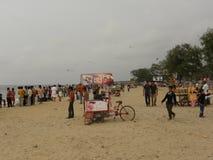 科泽科德,喀拉拉,印度-科泽科德的2009 1月1日,人在背景中靠岸与黑暗的云彩 免版税库存照片