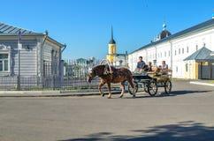 科洛姆纳,俄罗斯- 2018年8月11日 有马车夫和马运载的游人的支架在老镇的街道下 免版税库存图片