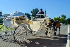 科洛姆纳,俄罗斯- 2018年8月11日 有马车夫的典雅的白色支架搭载游人的黑帽会议和棕色马的 库存图片