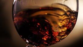 科涅克白兰地在玻璃被转动 在黑暗的背景 影视素材