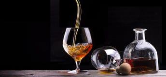 科涅克白兰地或白兰地酒在一张木桌上 免版税库存图片