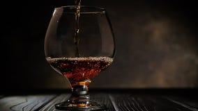 科涅克白兰地涌入玻璃 在黑暗的背景 影视素材