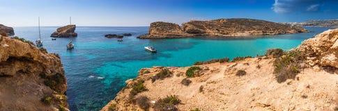 科米诺岛,马耳他-有绿松石明白海水、游艇和潜航的游人的美丽的蓝色盐水湖在一个晴朗的夏天 免版税库存图片