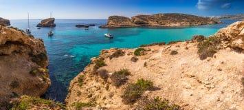 科米诺岛,马耳他-有绿松石明白海水、游艇和潜航的游人的美丽的蓝色盐水湖 免版税库存照片