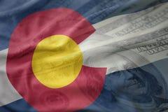 科罗拉多状态五颜六色的挥动的旗子在美国美元金钱背景的 免版税图库摄影