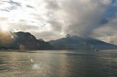 科莫湖看法在与小船的一多云天在前景在贝拉焦 库存图片