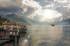 科莫湖看法在与汽艇和港口的一多云天在贝拉焦 免版税库存图片