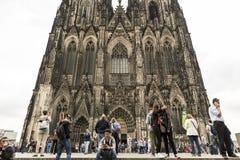 科隆,德国, 2017年7月2日:有手机的未认出的人在著名大教堂前面 免版税图库摄影