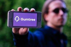 科隆,德国- 2018年5月30日:严肃的年轻人特写镜头有举行与GUMTREE商标的太阳镜的白色iPhone在屏幕上 免版税图库摄影