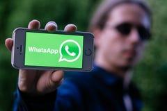 科隆,德国- 2018年5月30日:严肃的年轻人特写镜头有举行与WHATSAPP商标的太阳镜的白色iPhone在屏幕上 库存图片