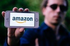 科隆,德国- 2018年5月06日:年轻人特写镜头有举行与亚马逊商标的太阳镜的白色iPhone在屏幕上 免版税库存图片