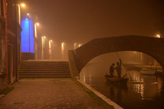科马基奥,运河桥梁的夜视图,小船的人们 冬天雾 免版税图库摄影