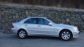 科鲁Napoca/罗马尼亚3月31日2017年:奔驰车W203 -年2005年,先驱设备,在岩石墙壁p附近的银色金属油漆 免版税库存照片