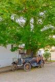 科洛尼亚德尔萨克拉门托,乌拉圭- 2016年5月04日:古老经典汽车停放了在树下在边路旁边 免版税库存照片