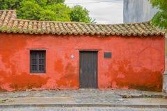 科洛尼亚德尔萨克拉门托,乌拉圭- 2016年5月04日:有一个标志的小矮小的红色房子在说的门旁边年,当时 库存照片