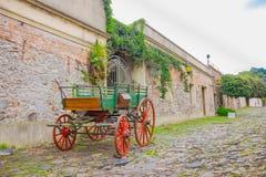 科洛尼亚德尔萨克拉门托,乌拉圭- 2016年5月04日:有红色轮胎的老绿色推车停放了一个古老房子外 免版税库存照片