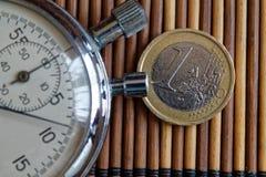 秒表和硬币与1欧元的衡量单位在木桌背景 免版税库存照片